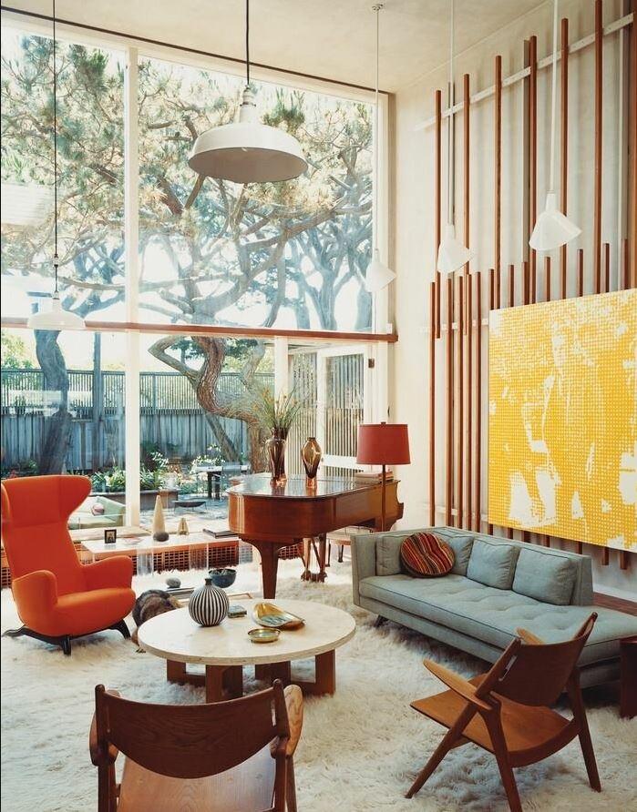 Фото гостинной выполненной по дизайн-проекту в стиле Mid-century modern. В светлых тонах. Яркий декор.