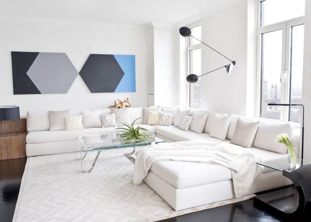Современная картина и стильный ковёр в интерьере где преимущественно белый цвет.